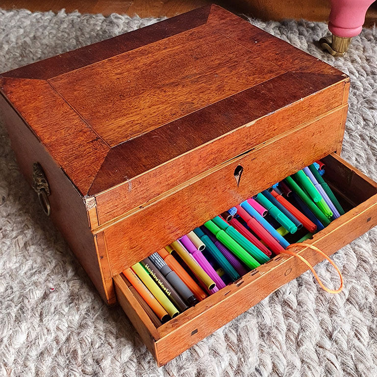 antique wooden box on wool rug filled with colour felt tips