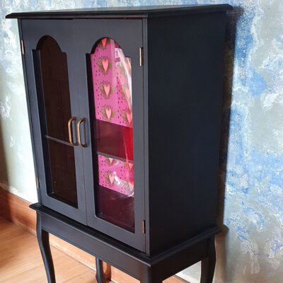black display cabinet from side closed doors against blue wall