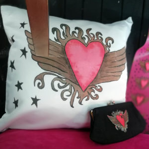 a white cushion with a heart design on it and a purse with the same heart design, both sitting on a pink surface