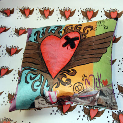 plumped cushion with heart with wings cushion on heart background