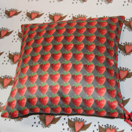 cushion cover with strawberries on charcoal background, background has heart design