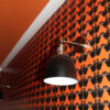 Maude Petite Wallpaper in Orange, showing white cornice and wall light