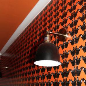 Maude Petite Wallpaper in Orange, showing white cornice and wall light