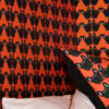 Maude Petite Wallpaper in Orange showing corner of a matching cushion and white pillows