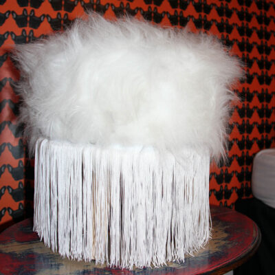 white faux fur and tassel footstool with franchise bulldog wallpaper in the background