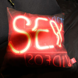 45cm cushion with the word sex in neon lights on it, resting on black sheets