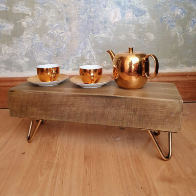 small table made from train sleeper on hairpin legs two gold cups and tea pot sitting on top