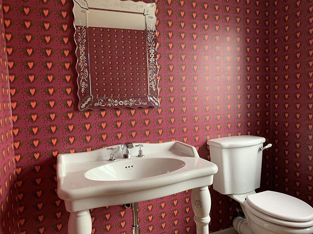 graffiti heart wallpaper by Claire Swindale in cloakroom with mirror white sink and toilet